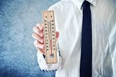 image of freezing temperatures  - Businessman holding thermometer with temperature on Zero value - JPG
