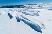 stock photo of windswept  - Windswept snow and view to Mt Bogong from above Falls Creek - JPG