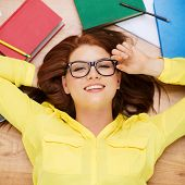 education and home concept - smiling redhead female student in eyeglasses lying on floor