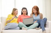 friendship, money, technology and internet concept - three smiling teenage girls with laptop compute