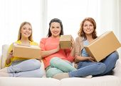 transportation, post and friendship concept - three smiling teenage girls with cardboard boxes at ho