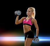 fitness, exercising and dieting concept - sporty woman with heavy steel dumbbells