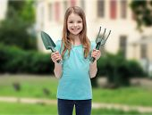 garden and people concept - smiling little girl with rake and scoop