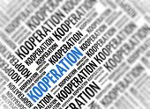 Background with german word - Kooperation (Cooperation) - repeated in random sizes and orientations in black text with one central word in large blue uppercase lettering and selective focus