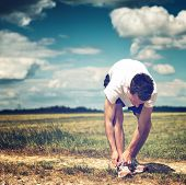 Sportsman on a rural track in open countryside bending over tying his laces on his running shoes before commencing his workout and training, square format with copyspace