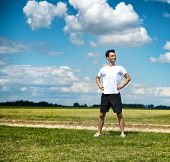 Fit proud determined young male athlete standing with his hands on his hips in open countryside alon
