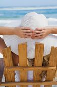 Woman sitting in deck chair at the beach on a sunny day