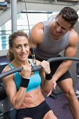 Female bodybuilder using weight machine for arms with encouraging trainer at the gym