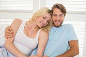 Young couple sitting on the couch smiling at camera at home in the living room