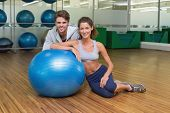 Fit woman leaning on exercise ball with trainer smiling at camera at the gym