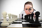 Composite image of thinking businesswoman with magnifying glass with chessboard