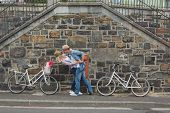 Hip young couple dancing by brick wall with their bikes on a sunny day in the city
