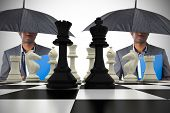 Businessman standing under umbrella with chessboard against white background with vignette