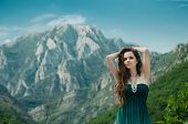 Beauty Girl Outdoors Enjoying Nature Over Mountain. Beautiful Teenage Model In Long Dress