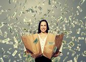 alluring smiley businesswoman holding two paper bags with money under dollar's rain