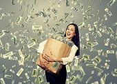 excited young businesswoman standing under dollar's rain and holding big paper bag with money