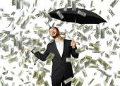 smiley glad businessman with umbrella standing under money rain and looking up