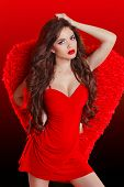 Beautiful Brunette Fashion Girl Model Posing In Red Dress With Wings. Victoria Style