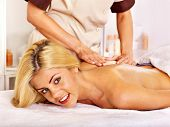 Blond woman getting massage in health resort.