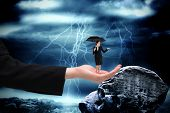 Young businesswoman holding umbrella in large hand against large rock overlooking stormy sky
