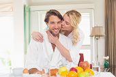 Cute couple in bathrobes having breakfast together at home in the living room