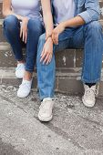 Hip young couple in denim sitting on steps on a sunny day in the city