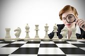 Composite image of focused businesswoman with magnifying glass with chessboard