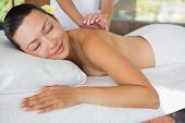 Smiling brunette getting a shoulder massage at the health spa