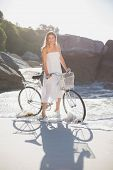 Beautiful blonde in white sundress standing with bike on the beach on a sunny day