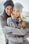 Cute couple in warm clothing smiling at camera on a chilly day