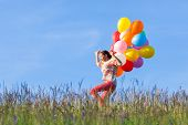 Outdoor Portrait Of A Young African American Teenage Girl Running With Balloons