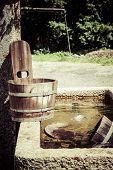 Old waterhole and old wooden bucket in Switzerland, Franc, Europe.