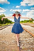 Beautiful woman with blue dress and hat on a train station.