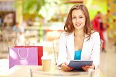 Shopping girl with touchpad looking at camera with smile
