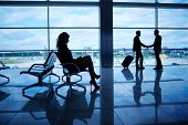 Outline of businesswoman sitting in airport on background of her colleagues handshaking by the windo