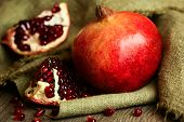 Ripe bright red pomegranate with seeds on wooden and sacking background