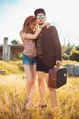 Girl And Guy With A Suitcase Outdoors