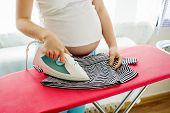 Pregnant woman ironing