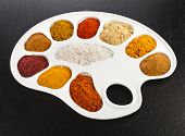 Collection of various colorful spices on a cooking palette on black wooden surface table