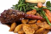 stock photo of lamb shanks  - Lamb Shank in a Rosemary and Red Wine Jus with vegetable on a white plate