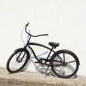 Black City Bicycle Cruiser Standing By Next White Wall
