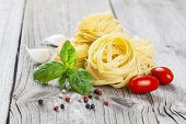 Italian Pasta Fettuccine Nest With Garlic, Tomatoes And Fresh Basil Leaves