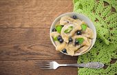 Dumplings with blueberries on wooden background