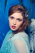 Romantic portrait of a young woman with braid hairstyle and luxury hair accessories on blue grunge texture background