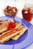 russian food - meat wrapped in a pancake with red hot pepper  and pickled mushrooms served on blue p