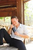 young happy white Caucasian man taste and enjoy red wine outdoor in in countryside . classic style f