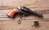 picture of revolver  - A 22 caliber revolver with bullets on a wooden background - JPG