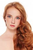 Young beautiful girl with long red hair and freckles over white background