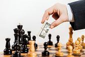Business man hand holding dollar currency unfair playing chess game
