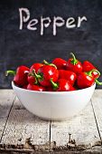 red hot peppers in bowl and blackboard on rustic wooden table
